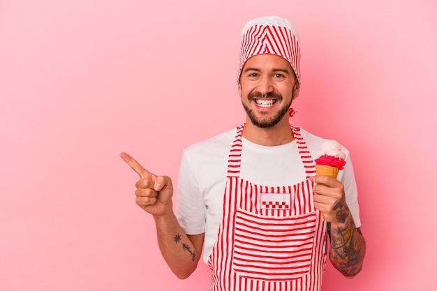 Młody kaukaski mężczyzna do lodu z tatuażami, trzymający lody na białym tle na różowym tle, uśmiechający się i wskazujący na bok, pokazując coś w pustej przestrzeni.