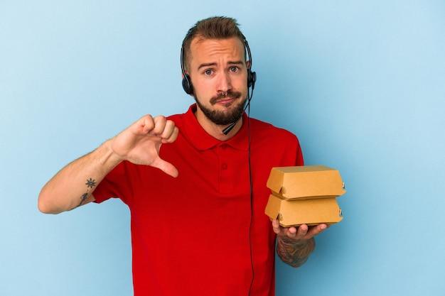 Młody kaukaski mężczyzna dostawy z tatuażami, trzymając hamburgery na białym tle na niebieskim tle pokazując gest niechęci, kciuk w dół. koncepcja niezgody.