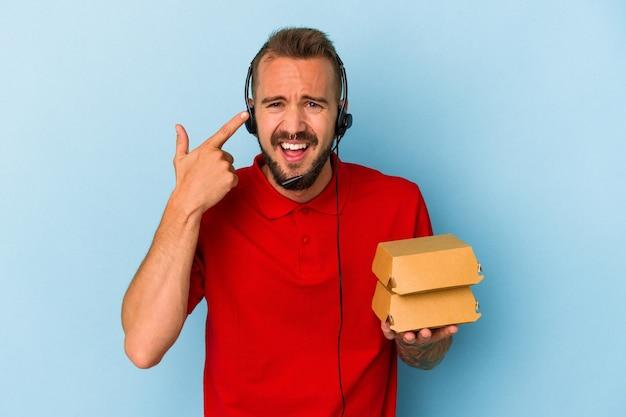 Młody kaukaski mężczyzna dostawy z tatuażami, trzymając hamburgery na białym tle na niebieskim tle pokazując gest rozczarowania palcem wskazującym.