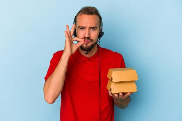 Młody kaukaski mężczyzna dostawy z tatuażami, trzymając hamburgery na białym tle na niebieskim tle z palcami na ustach, zachowując tajemnicę.