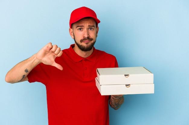 Młody kaukaski mężczyzna dostawy z tatuażami, trzymając pizze na białym tle na niebieskim tle pokazujący gest niechęci, kciuk w dół. koncepcja niezgody.