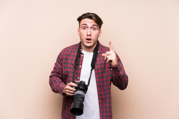 Młody kaukaski mężczyzna fotograf na białym tle pomysł, koncepcja inspiracji.