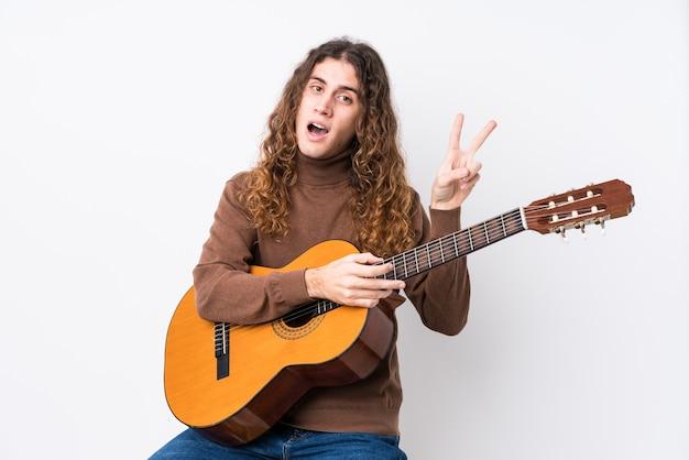 Młody kaukaski mężczyzna gra na gitarze na białym tle radosny i beztroski pokazując palcami symbol pokoju.