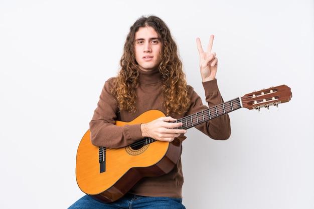 Młody kaukaski mężczyzna gra na gitarze na białym tle wyświetlono numer dwa palcami.