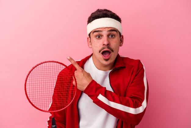 Młody kaukaski mężczyzna gra w badmintona na białym tle na różowym tle, wskazując na bok