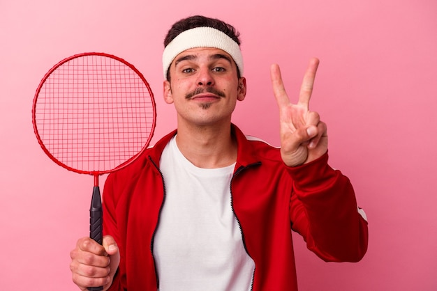 Młody kaukaski mężczyzna gra w badmintona na białym tle na różowym tle wyświetlono numer dwa palcami.