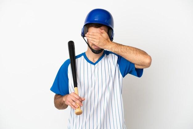 Młody kaukaski mężczyzna gra w baseball na białym tle na białym tle obejmujące oczy rękami. nie chcę czegoś widzieć