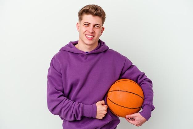Młody kaukaski mężczyzna gra w koszykówkę na białym tle ściany śmiejąc się i zabawy
