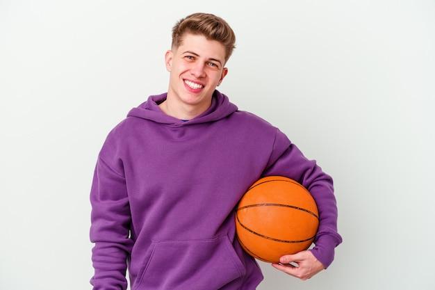Młody kaukaski mężczyzna gra w koszykówkę na białym tle szczęśliwy, uśmiechnięty i wesoły.