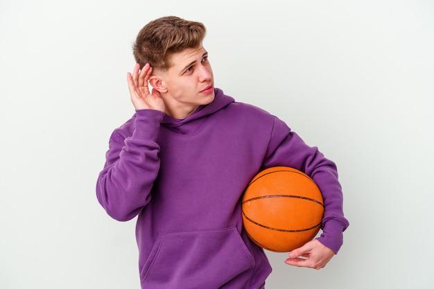 Młody kaukaski mężczyzna gra w koszykówkę, próbując słuchać plotek.