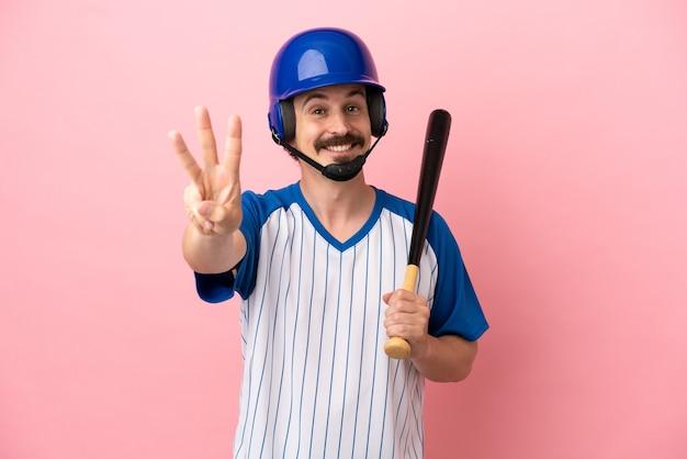 Młody kaukaski mężczyzna grający w baseball na białym tle na różowym tle szczęśliwy i liczący trzy palcami