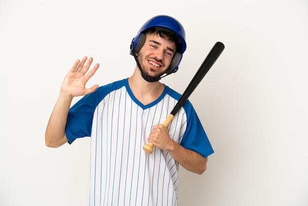 Młody kaukaski mężczyzna grający w baseball na białym tle pozdrawiając ręką ze szczęśliwym wyrazem twarzy