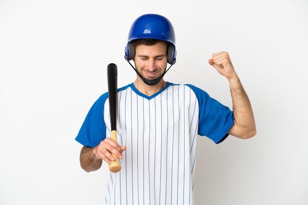 Młody kaukaski mężczyzna grający w baseball na białym tle robi silny gest