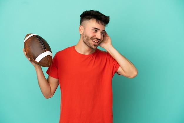 Młody kaukaski mężczyzna grający w rugby na białym tle na niebieskim tle, słuchając czegoś, kładąc rękę na uchu