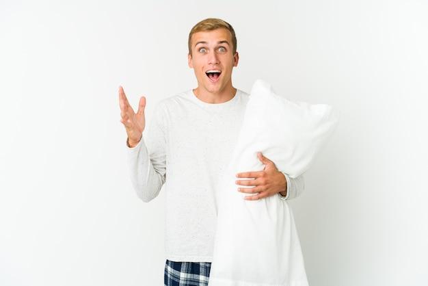 Młody kaukaski mężczyzna idzie spać na białym tle na białej ścianie, otrzymując miłą niespodziankę, podekscytowany i podnoszący ręce.