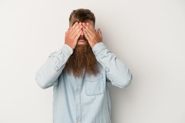 Młody kaukaski mężczyzna imbir z długą brodą na białym tle boi się zasłaniając oczy rękami.