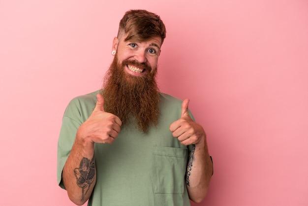 Młody kaukaski mężczyzna imbir z długą brodą na białym tle na różowym tle podnosząc oba kciuki do góry, uśmiechnięty i pewny siebie.