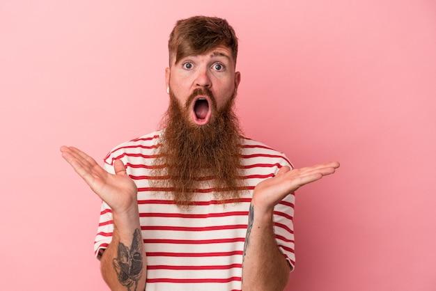 Młody kaukaski mężczyzna imbir z długą brodą na białym tle na różowym tle zaskoczony i zszokowany.