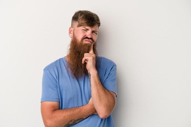 Młody kaukaski mężczyzna imbir z długą brodą na białym tle niezadowolony patrząc w aparacie z sarkastycznym wyrazem.