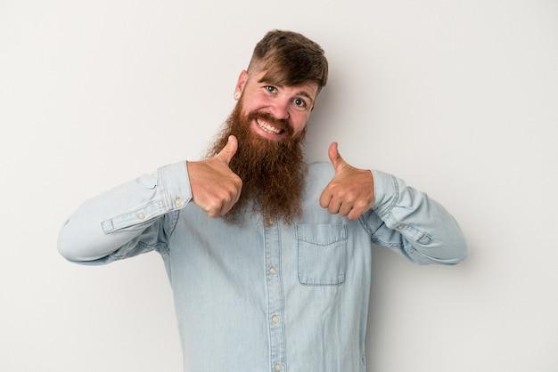 Młody kaukaski mężczyzna imbir z długą brodą na białym tle podnosząc oba kciuki do góry, uśmiechnięty i pewny siebie.