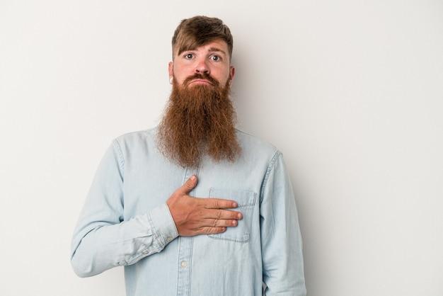 Młody kaukaski mężczyzna imbir z długą brodą na białym tle składa przysięgę, kładąc rękę na klatce piersiowej.