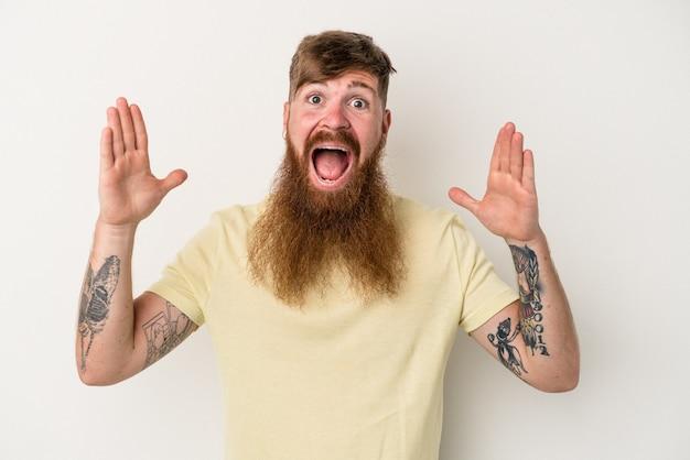 Młody kaukaski mężczyzna imbir z długą brodą na białym tle świętuje zwycięstwo lub sukces, jest zaskoczony i zszokowany.