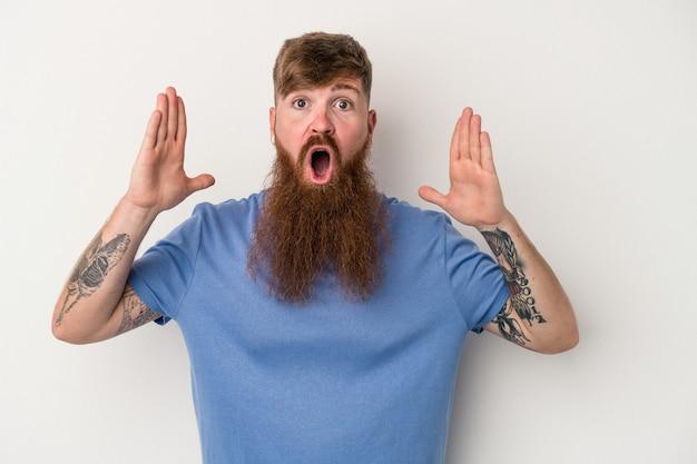 Młody kaukaski mężczyzna imbir z długą brodą na białym tle zaskoczony i zszokowany.