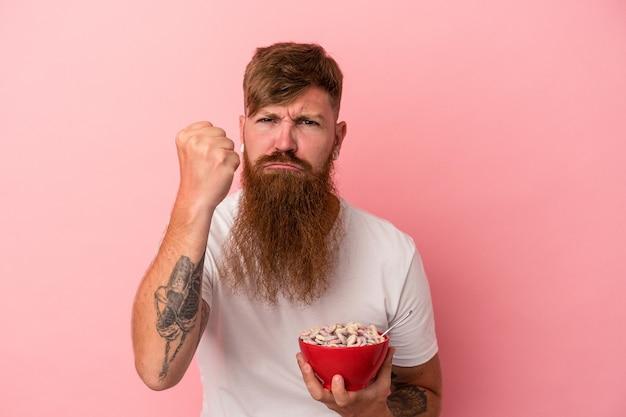 Młody kaukaski mężczyzna imbir z długą brodą trzyma miskę zbóż na białym tle na różowym tle pokazując pięść do aparatu, agresywny wyraz twarzy.