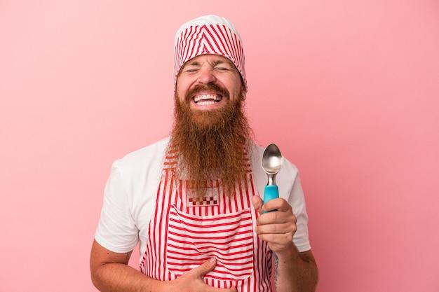 Młody kaukaski mężczyzna imbir z długą brodą, trzymając gałkę na białym tle na różowym tle, śmiejąc się i bawiąc.