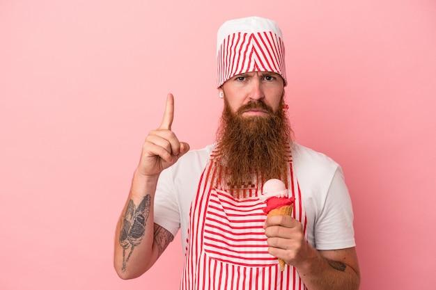 Młody kaukaski mężczyzna imbir z długą brodą, trzymając lody na białym tle na różowym tle pokazując numer jeden palcem.