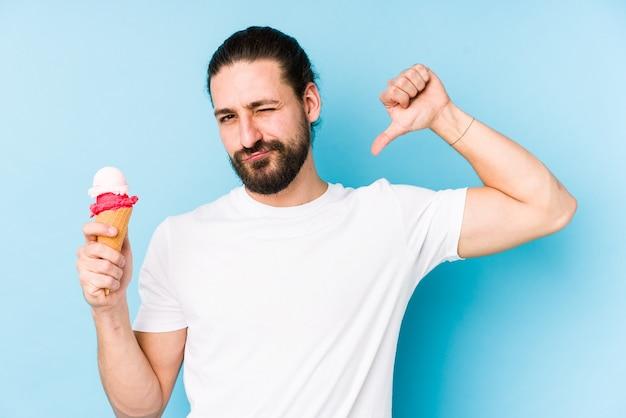 Młody kaukaski mężczyzna jedzący lody na białym tle czuje się dumny i pewny siebie - przykład do naśladowania.