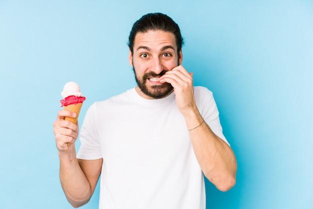 Młody kaukaski mężczyzna jedzenie lodów obgryzających paznokcie, nerwowy i bardzo niespokojny.