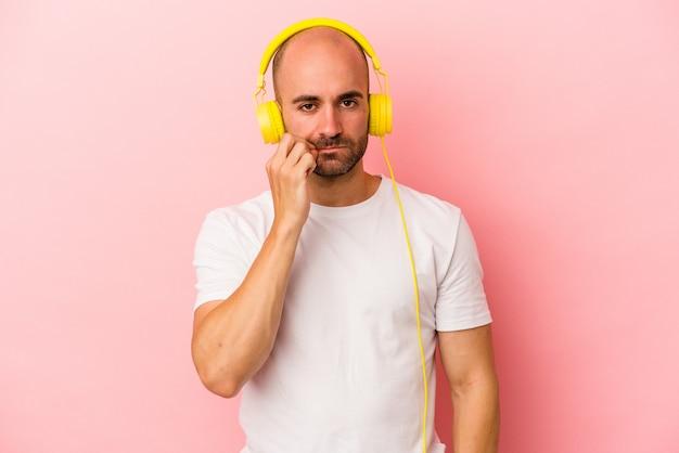 Młody kaukaski mężczyzna łysy słuchanie muzyki na białym tle na różowym tle palcami na ustach zachowując tajemnicę.