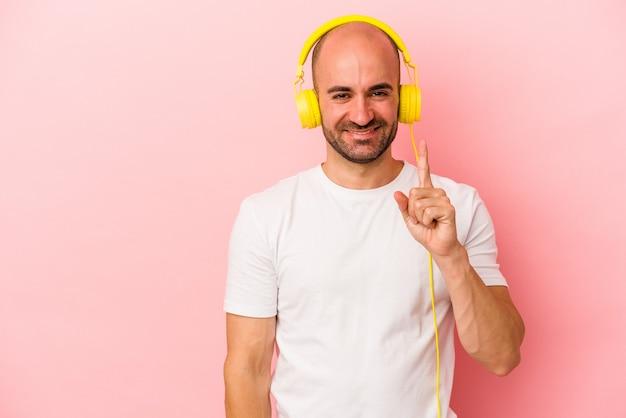 Młody kaukaski mężczyzna łysy słuchanie muzyki na białym tle na różowym tle pokazując numer jeden palcem.