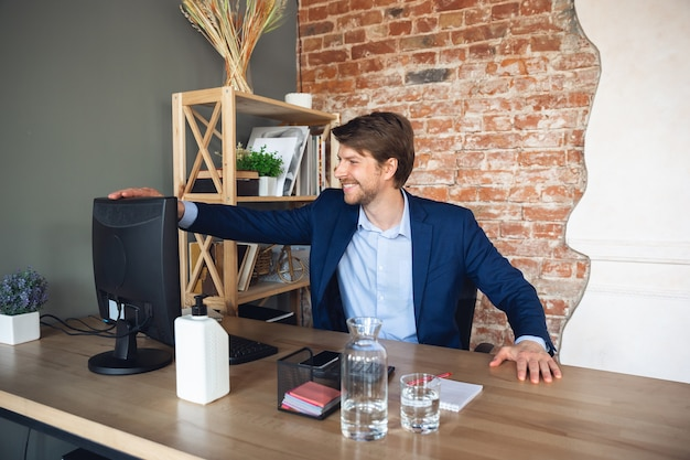 Młody kaukaski mężczyzna, menedżer, kierowany zespołem powrót do pracy w swoim biurze po kwarantannie