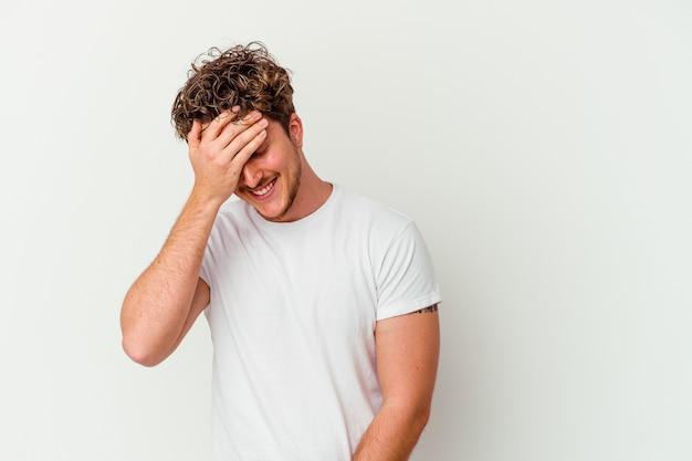 Młody kaukaski mężczyzna na białej ścianie mruga do kamery palcami, zawstydzona zakrywająca twarz.
