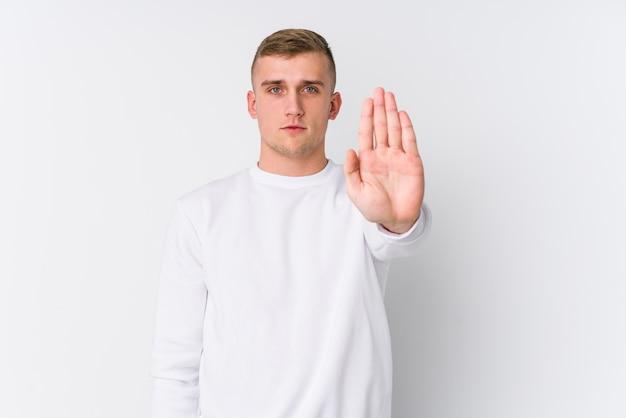 Młody kaukaski mężczyzna na białym stojącym z wyciągniętą ręką pokazując znak stopu, uniemożliwiając ci.