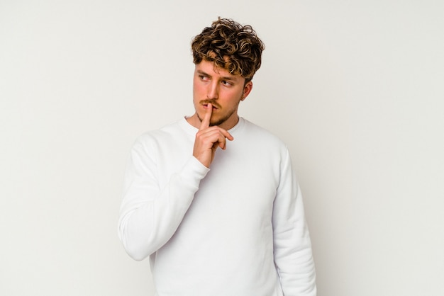 Młody kaukaski mężczyzna na białym tle dochowując tajemnicy lub prosząc o ciszę.