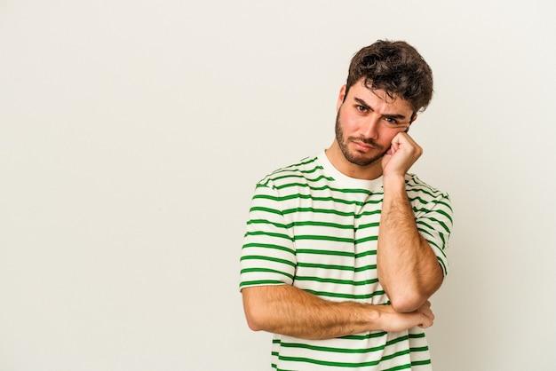 Młody kaukaski mężczyzna na białym tle, który czuje się smutny i zamyślony, patrząc na miejsce.