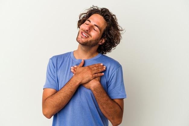 Młody kaukaski mężczyzna na białym tle ma przyjazny wyraz twarzy, przyciskając dłoń do klatki piersiowej. koncepcja miłości.