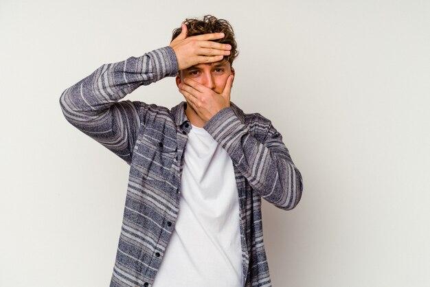 Młody kaukaski mężczyzna na białym tle mruga do aparatu przez palce, zawstydzony zakrywający twarz.