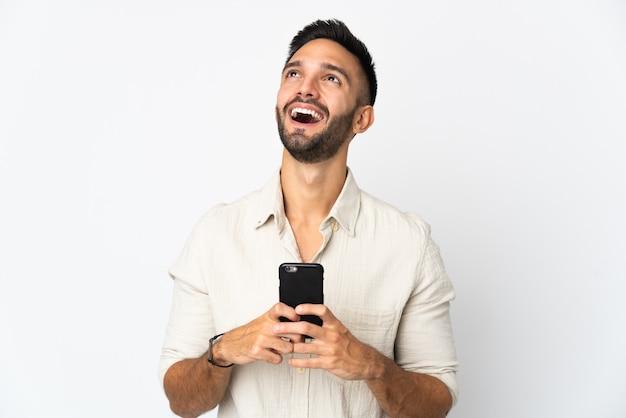 Młody kaukaski mężczyzna na białym tle na białej ścianie przy użyciu telefonu komórkowego i patrząc w górę