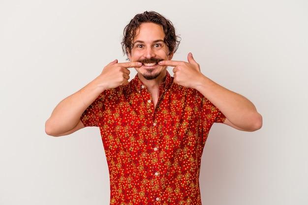 Młody kaukaski mężczyzna na białym tle na białej ścianie uśmiecha się, wskazując palcami na usta