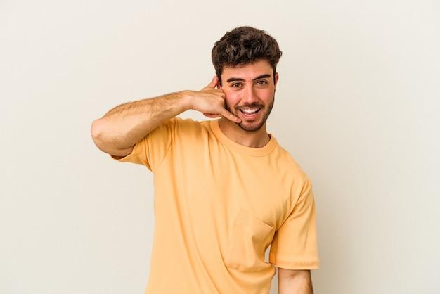 Młody kaukaski mężczyzna na białym tle na białym tle pokazując gest połączenia z telefonu komórkowego palcami.