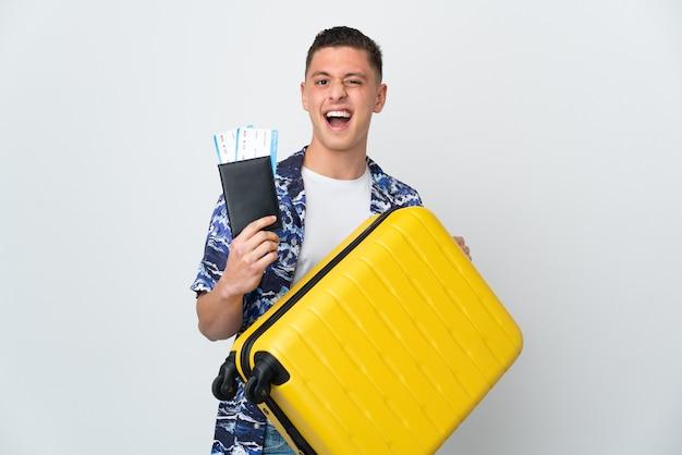 Młody kaukaski mężczyzna na białym tle na białym tle w wakacje z walizką i paszportem