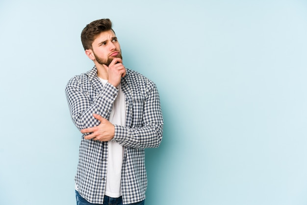 Młody kaukaski mężczyzna na białym tle na niebieskiej przestrzeni, patrząc z boku z wątpliwym i sceptycznym wyrazem.