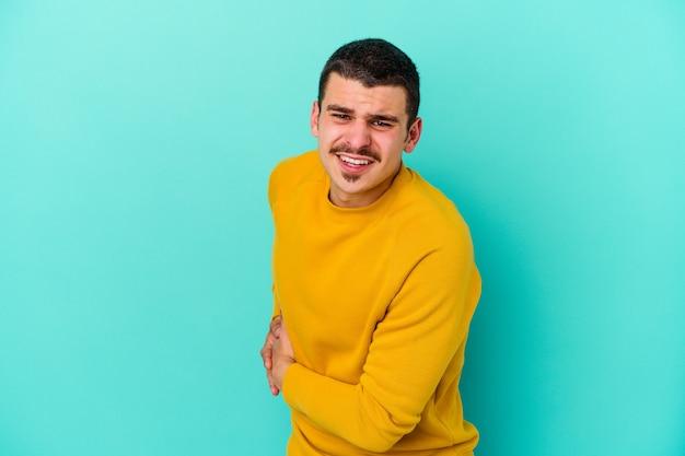 Młody kaukaski mężczyzna na białym tle na niebieskiej ścianie o ból wątroby, ból brzucha.