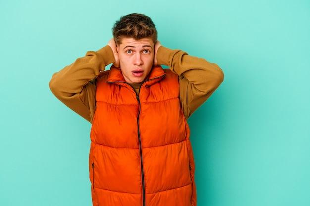 Młody kaukaski mężczyzna na białym tle na niebieskiej ścianie obejmujące uszy rękami, starając się nie słyszeć zbyt głośnego dźwięku