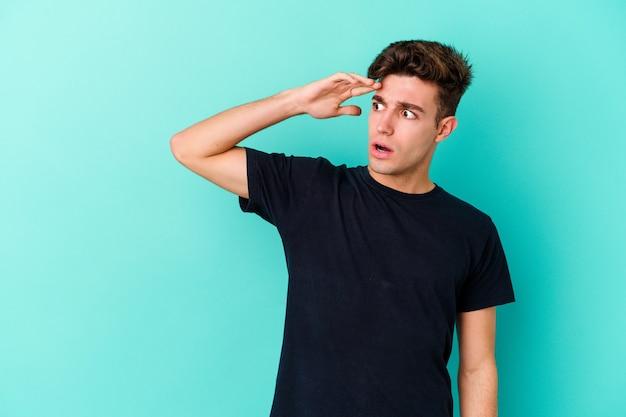 Młody kaukaski mężczyzna na białym tle na niebieskiej ścianie, patrząc daleko, trzymając rękę na czole