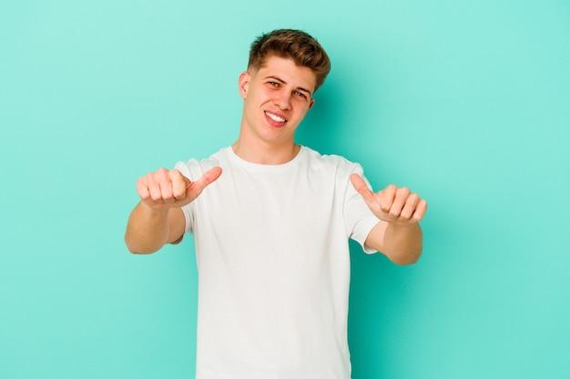 Młody kaukaski mężczyzna na białym tle na niebieskiej ścianie, podnosząc oba kciuki do góry, uśmiechnięty i pewny siebie